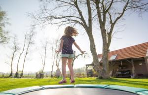 Nena que salta en un llit elàstic a l'exterior d'una casa