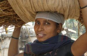 Pagesa carregant un feix de palla al cap. Il·lustra un article sobre el consum feminista.