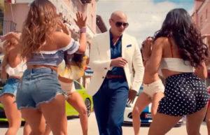 Chicas con pantalón corto bailando reguetón alrededor de un hombre calvo.