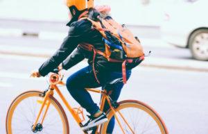 Ciclista con mochilla naranja y negra. Moverse en bicicleta es una forma de hacer salud.