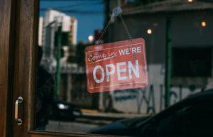 Cartel rojo con palabra Open en puerta tienda. Día sin compras.