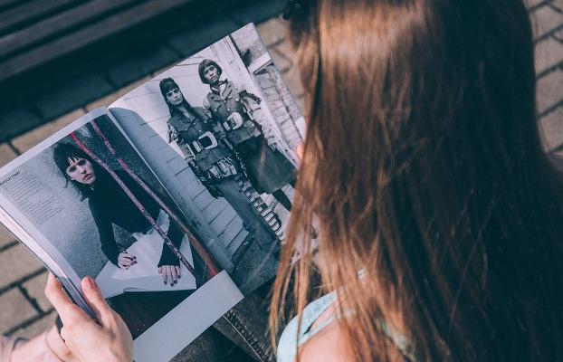 Mujer leyendo revistas femeninas.