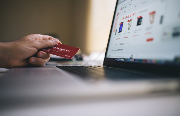 Comercio digital en la pantalla de un portátil cuyo usuario tiene una tarjeta de crédito en la mano