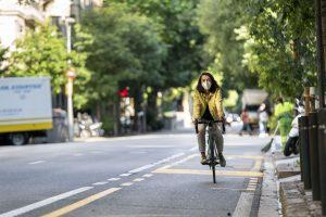 Una ciclista amb mascareta circula per Barcelona. Foto: Mònica Moreno